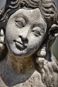 Face of stone old grey female statue with gentle smile